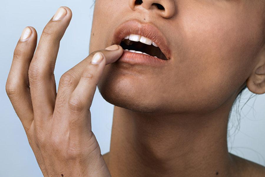 Closeup of a woman applying a lip balm on her lip